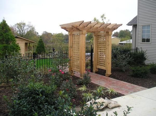 Free-standing cedar pergola with brick walkway.