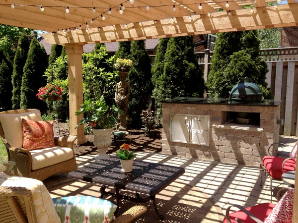 Custom cedar pergola over top a Unilock patio and custom granite topped Green Egg grill island.